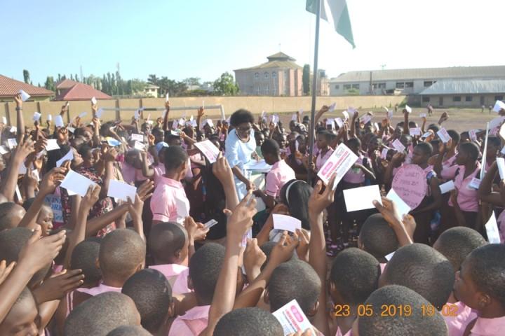 Executive Director WINET Miriam Menkiti giving MENSTRUAL Hygiene Day stickers to students of Girls High School Uwani Enugu, Enugu State Nigeria